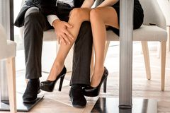 Legs of a couple sitting at the restaurant stock images