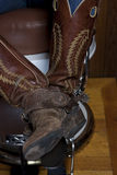 Legs With Cowboy Boots In a Shoeshine Chair Royalty Free Stock Photos