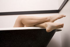 Legs crossed edge tub stock photography