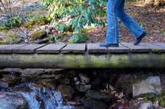Legs Crossing Foot Bridge. Legs are shown walking over a wooden foot bridge crossing a small stream in the country Royalty Free Stock Image