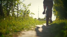 Legs of cyclists, two young girls passing on a path in a green forest on a Sunny day. Slow-motion stock footage