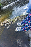 Legs dangle over the edge of a river Stock Photography