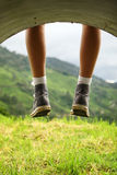 Legs dangling. Freely against green landscape royalty free stock photo