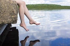 Legs dangling over water Stock Photo
