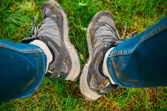 Legs in dirty shoes and jeans while hiking Stock Images