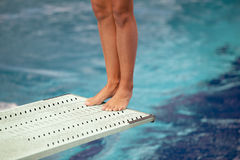 Legs on a diving board. Girl standing on diving board, preparing to dive Royalty Free Stock Photos