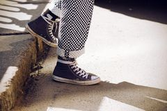 Legs dressed in plaid pants and in blue sneakers descend from the step royalty free stock images
