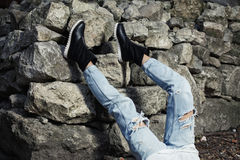Legs dressed in ripped blue jeanswith black stylish boots. Studio photo on rock wall background stock images