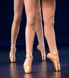 Legs of duo of ballerinas on pointe. Staying on dark blue floor Stock Photo