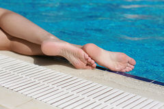 Legs on edge the pool. With blue water Royalty Free Stock Photography