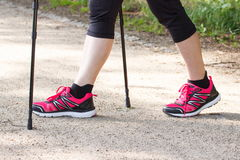 Legs of elderly senior woman practicing nordic walking, sporty lifestyles in old age. Legs of elderly senior woman in sporty shoes practicing nordic walking Stock Images