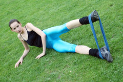 Legs exercise with a band. A young girl doing legs exercises in the open air with the elastic band Royalty Free Stock Photos