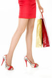 Legs of the fan of shopping. Side view of female legs, hands hold the gift packages, isolated Stock Photos