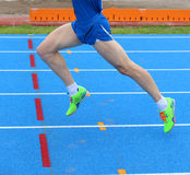 Legs of fast runner runs into the in athletics track. Long legs of fast runner runs into the blue in athletics track Royalty Free Stock Photography
