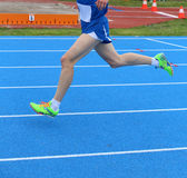Legs of fast runner runs into the blue in athletics track. Long legs of fast runner runs into the blue in athletics track Stock Photos