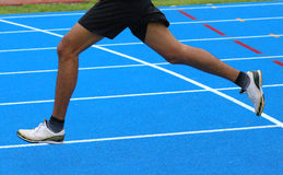 Legs of fast runner runs into the blue in athletics track. Long legs of fast runner runs into the in athletics track Royalty Free Stock Image
