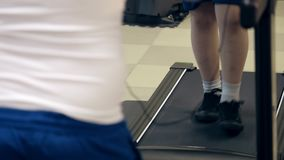 Legs of fat boy in sneakers walking on treadmill during cardio workout in gym indoors. Legs of fat boy in sneakers walking on the treadmill during cardio workout stock footage