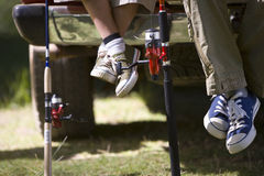 Legs of father and son next to fishing poles Royalty Free Stock Photography
