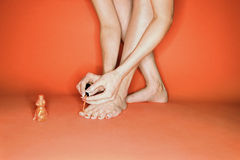 Legs and feet of Caucasian woman painting her toenails. Legs and feet of  Caucasian mid-adult woman on orange background painting her toenails with nail polish Royalty Free Stock Photos