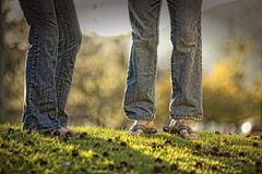 Legs and feet of couple in jeans Stock Photos