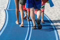 Legs and feet of a family walking. Along the blue access path on the sandy beach headed for some fun in the sun royalty free stock photography