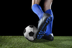 Legs and feet of football player in action running and dribbling with the ball playing on green grass Royalty Free Stock Photography