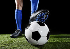Legs and feet of football player in blue socks and black shoes posing with the ball playing on green grass. Close up legs and feet of football player in blue royalty free stock image