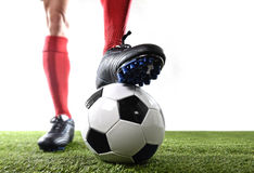 Legs feet of football player in red socks and black shoes posing with the ball playing on green grass pitch royalty free stock photo