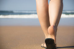 Legs and feet of a girl walking towards the sea Stock Images