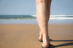 Legs and feet of a girl walking towards the sea Royalty Free Stock Image