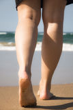Legs and feet of a girl walking towards the sea Stock Image