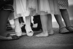 Legs and feet of little girls in line. A group of girls are sitting and standing on bench with their legs inlined royalty free stock photography