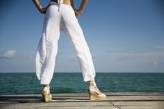 Legs and feet of a pretty girl. Wide stance of a healthy and fit girl looking over the water with plenty of room for text and a wide range of concept Stock Photos