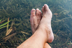 Legs and feet relaxing in front of serene fresh water pond Stock Images