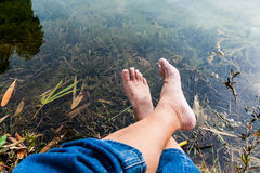 Legs and feet relaxing in front of serene fresh water pond Stock Photo