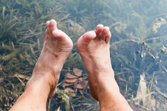 Legs and feet relaxing in front of serene fresh water pond Stock Photos