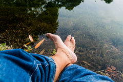 Legs and feet relaxing in front of serene fresh water pond Royalty Free Stock Image