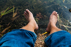 Legs and feet relaxing in front of serene fresh water pond Royalty Free Stock Photography