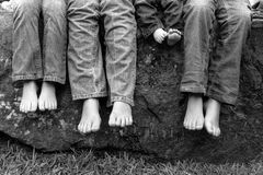 Legs and feet of siblings sitting on rock. A black and white image of legs and feet of siblings wearing blue jeans and sitting on a rock Royalty Free Stock Image
