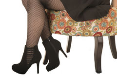 Legs and feet of a woman sitting in floral chair with high heels Stock Image