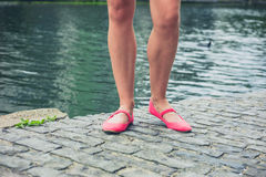 Legs and feet of young woman by canal Royalty Free Stock Images