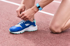 Legs of female runner adjusting shoelaces on running shoe. Close up of feet of young woman tying laces on her sneaker. She is kneeling on track wearing stock photo