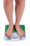 Legs of female standing on bathroom scales Royalty Free Stock Images
