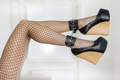 Legs in fishnet stockings, ankle cuffs and high heels Royalty Free Stock Images