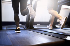 Legs of Fit Couple Exercising on Treadmill Device Stock Images