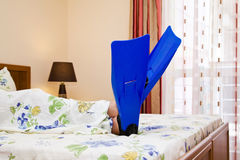 Legs in flippers on bed. Legs with flippers in bedroom lying on the bed Royalty Free Stock Photos