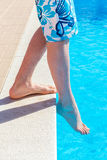Legs with foot feeling water temperature in swimming pool Stock Image