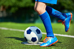 Legs football player boy in boots with ball on grass Royalty Free Stock Photography
