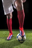 Legs of footballer. With a ball on the field royalty free stock photo