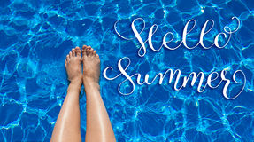 Legs girl on a background of pool water and letters Hello Summer Royalty Free Stock Photos